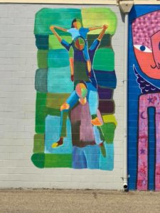 Family Joy mural in downtown New Philadelphia, Ohio depicting family on each other's shoulders
